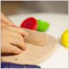 ウッデントイの木製のおもちゃままごとで野菜を切る子ども